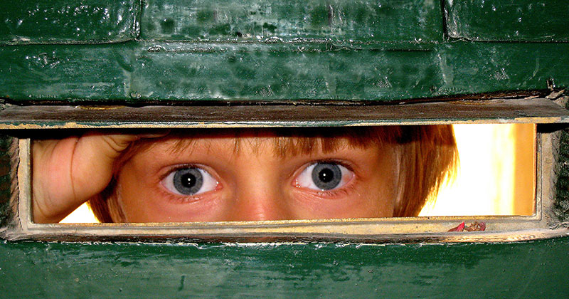 Boy looking through letter slot